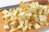 detail of cubed celery and kitchen knife on wooden cutting board