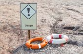 Two Life Buoys Orange And White On The Rock With Danger Sign Are Creating Safety Awareness.