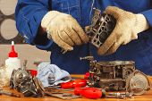 Master repairing old car engine carburetor