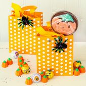 Halloween children's treat bags decorated with spiders and filled with chocolates and candy.