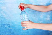 Hand holds bottle with water on blue background