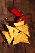 pic of nachos  - Tasty nachos and chili pepper on wooden background - JPG