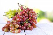 Bunches of ripe grape in wicker basket on wooden table on natural background