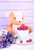 Toy bear with flowers and cup of raspberries on wooden wall background
