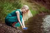 beautiful young blond woman with a paper boat by the lake in summertime