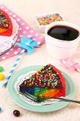 Delicious rainbow cake on plate and cup with coffee, on table, on light background