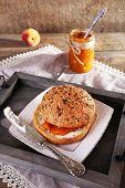 tasty bun with homemade jam on wooden table