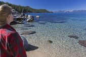 Woman Looking Over Beautiful Clear Water Shoreline of Lake Tahoe.