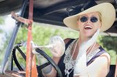 Attractive Young Woman in Twenties Outfit Driving an Antique Automobile.