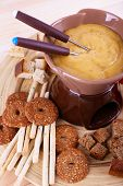 Fondue, biscuits, slices of cheese and rusks on bamboo plate on wooden background