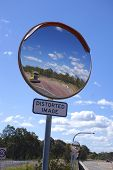 stock photo of distortion  - A large parking lot mirror with a distorted image warning sign - JPG
