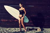attractive young woman in bikini and black top holding surfboard on sandy beach by wooden wall full body shot