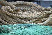 image of coiled  - Coiled ropes and fishing nets on fishing boat - JPG