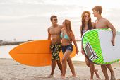 friendship, sea, summer vacation, water sport and people concept - group of smiling friends wearing