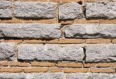 picture of gneiss  - Old stone wall with bricks closeup in sunny day - JPG