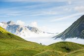 Low hanging clouds in La Peule valley, in Switzerland, with alps in the background. The region is one of the stages in the popular Mont Blanc tour, which crosses France, Italy and Switzerland.