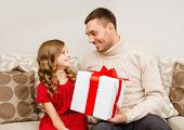 christmas, x-mas, winter, happiness and people concept - smiling father and daughter holding gift bo