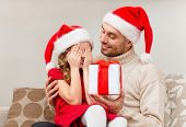 family, christmas, x-mas, happiness and people concept - smiling daughter with closed eyes waiting f