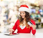 christmas, holidays, technology and shopping concept - smiling woman in santa helper hat with credit