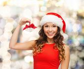christmas, holidays, winter, happiness and people concept - smiling woman in santa helper hat with j