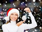winter, people, christmas and happiness concept - woman in santa helper hat with christmas tree deco