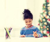 family, children, christmas, x-mas and happy people concept - little girl drawing