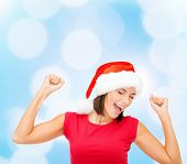 christmas, winter, holidays, happiness and people concept - smiling woman in santa helper hat and bl