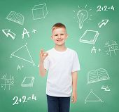 childhood, gesture, education, advertisement and people concept - smiling boy in white t-shirt showi