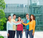 friendship, education, business, gesture and people concept - group of smiling teenagers making high