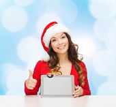 christmas, holidays, technology and people concept - smiling woman in santa helper hat with tablet p