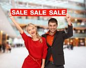 sale, christmas, holidays and people concept - smiling man and woman in red dress with red sale sign