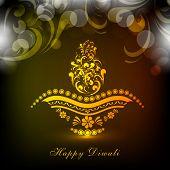 Golden floral design decorated illuminated lit lamp for Hindu community festival Happy Diwali celebr