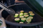 Zucchini being fried on grill at outdoor kitchen