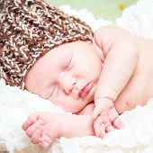 beautiful newborn baby boy sleeping in knitted cap close-up
