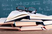 Books and glasses on wooden table on blackboard background