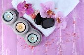 Orchid flowers, spa stones, candles and towel on color wooden background