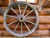 Hand Spinning Wheel On  Wall Of  Old Log House Village.