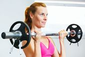 Woman exercising with barbell in gym.