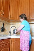 Woman Housewife Washing Dishes In The Kitchen