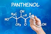 Hand with pen drawing the chemical formula of Panthenol