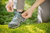 Woman Tying Walking Shoe Over Moss