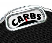 stock photo of carbohydrate  - Carbs word on a scale to illustrate eating too much carbohydrates in your diet and needing to cut on snack food and lose weight - JPG