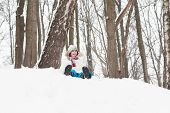 Happy Child Sledging From A Snowy Hill