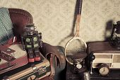 stock photo of untidiness  - Group of vintage assorted items on attic hardwood floor with vintage wallpaper background.