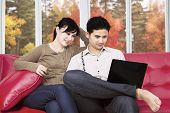 Couple Using Laptop At Home In Autumn