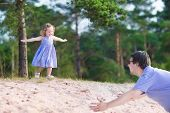Father And Daughter Playing In A Forest