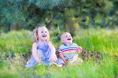 picture of little young child children girl toddler  - Happy little children adorable toddler girl in a blue dress and a cute baby boy brother and sister playing together with pine cones sitting in a sunny forest on a warm summer day - JPG