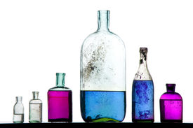 foto of mad scientist  - old perfumer bottles with colorful liquid on white - JPG
