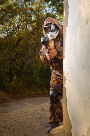 stock photo of paintball  - Paintball player with mask and his paintball gun - JPG