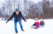 Young father with little daughters sledding in winter outdoors